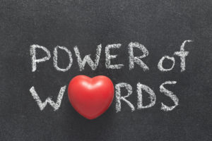 power of words phrase handwritten on blackboard with heart symbol instead of O